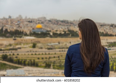 Girl watching the panoramic view of  Jerusalem Old city and the Temple Mount, Dome of the Rock and Al Aqsa Mosque from the Mount of Olives in Jerusalem, Israel.