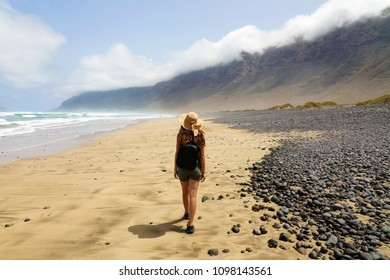 Girl is watching the suggestive landscape of Caleta Famara, Lanzarote, Canary Islands