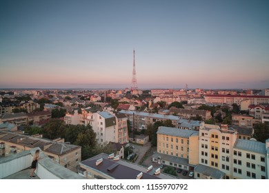 Girl watching sunset from aerial view  in european city