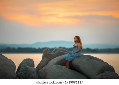 А girl is watching the sunset on the beach. The rocks on the Bank look like a huge blanket.  Image with selective focus, toning and noise effects.