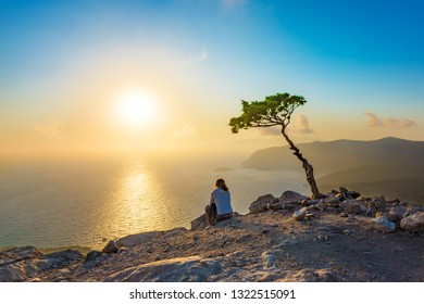 Girl watching sunset on Rhodes island seen from Monolithos castle (Rhodes, Greece)