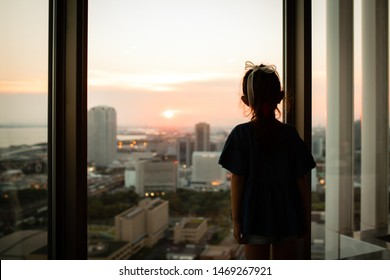 Girl watching the sunset from the window of the apartment