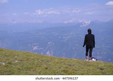 Girl watching the valley from the top of a mountain