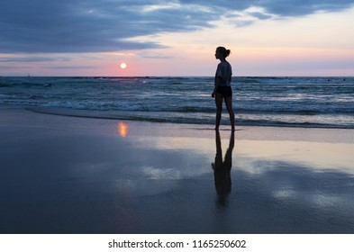 Girl in the water of the beach with the sun over the sea, city of San Sebastian, Basque country