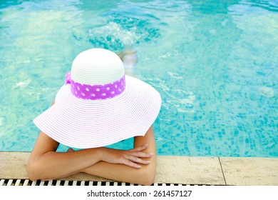 Girl in water pool in hat