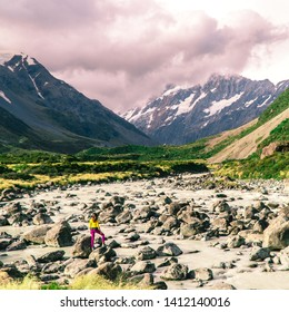 Girl in water stream on the Hooker trail tramping trek. Dramatic. Snow capped Mount Cook Mountain background. Grey cloudy moody. Green outdoors nature concept. Shot in Pukaki, New Zealand
