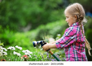 Girl watering flowers in garden with hose