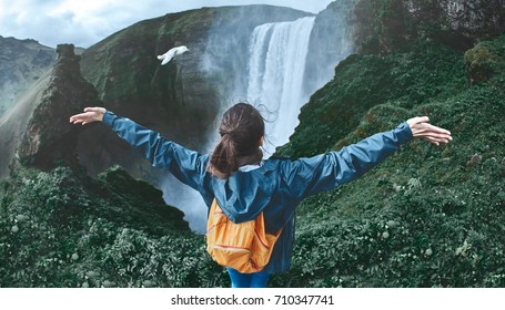 Girl in waterproof clothing sits on the cliff on background of Skogafoss waterfall in Iceland. View from above