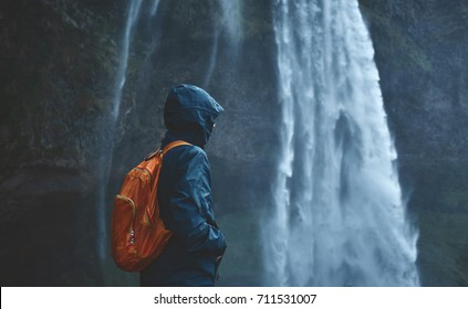 Girl in waterproof clothing stands under the Seljalandsfoss waterfall in Iceland. back view, woman with small orange backpack