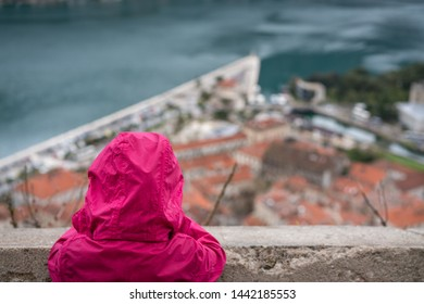 Girl in a waterproof pink jacket admiring stunning landscape of the Bay of Kotor, Montenegro