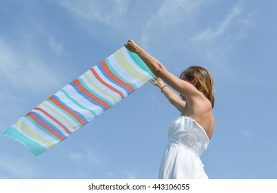 Girl waving a colorful scarf on seaside against blue sky