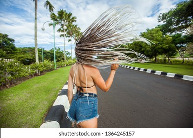 Girl waving dreadlocks on the background of palm trees