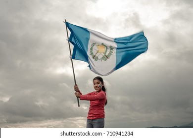 Girl waving a Guatemala's flag,  with sky background.