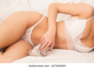 girl wear erotic lingerie and touch cat. fluffy and soft. feeling playful. for pussycat lovers. home care of body concept. cat and girl. sensual woman in lingerie. sexy woman with pet kitten.