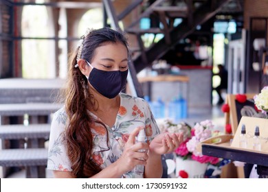 girl wear fabric face mask spraying  alcohol to clean hands before get in to restuarant