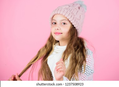Girl wear knitted hat pink background. Prevent winter hair damage. Winter hair care tips you should definitely follow. Winter time train yourself to go longer between washes. Child long hair smiling.