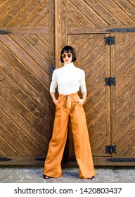Girl wear loose high waisted pants. Fashion shop. High waisted pants fashion trend. High waisted trousers. Woman attractive brunette wear fashionable clothes. Femininity and emphasize feminine figure.