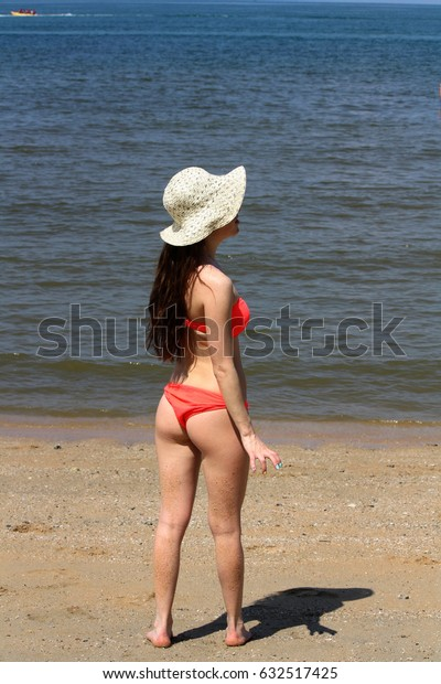 girl wear orange bikini and white hat stand on the beach