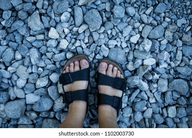 Girl wearing Birkenstock sandals whilst standing on grey stones and pebbles
