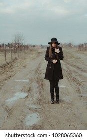 Girl wearing a black coat and hat