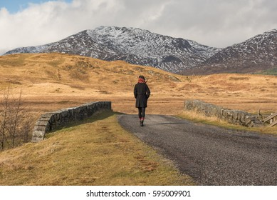 Girl wearing black jacket and scarf walks away on a road near the Bridge of Orchy, Argyll and Bute, Scotland, UK, where snowy mountains can be seen on a distant valley on the background.