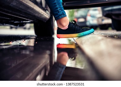 Girl wearing black sneakers stepping out of the car and avoiding puddle