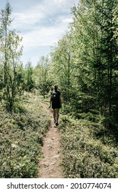 Girl wearing black walking along path in the forest. Slightly toned down colors. High Coast area, Sweden