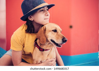 Girl wearing blue sun hat sitting on the deck floor of a ferry with a small brown dog with red wall in the background and looking at distance