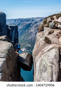 A girl wearing blue T-shirt standing with one leg on hanging rock, Kjerag, Norway. The ball-shaped rock is hanging in between stone walls with a free fall of 1000m. She is concentrated and cautious