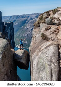 A girl wearing blue T-shirt standing on hanging rock, Kjerag, Norway. The ball-shaped rock is hanging in between stone walls with a free fall of 1000m. Happiness and freedom after stepping on the rock