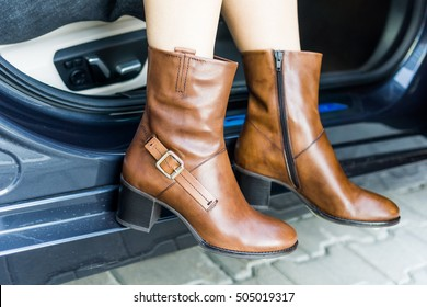 A girl wearing brown leather boots is getting out of a car on the street