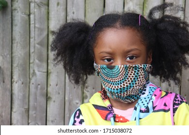 Girl Wearing Cloth Facemask outside wooden fence background