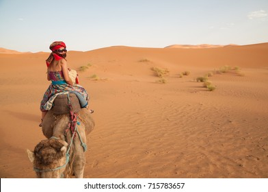 Girl wearing colourful clothes, a head scarf and harem pants rides a camel across the Sahara Desert in Morocco, North Africa, as she turns back to look at the camera that follows her on another camel