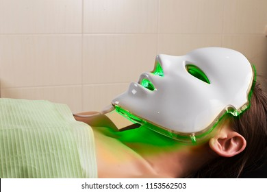 Girl is wearing cosmetic face photon mask.  Health and beauty. Cosmetic procedure for woman face. Beauty laboratory. LED Facial Mask, Photon Therapy. Photo shows the different modes, colors.