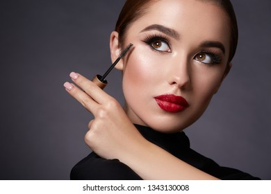 Girl wearing evening make up with long lashes at black background and using mascara, portrait.