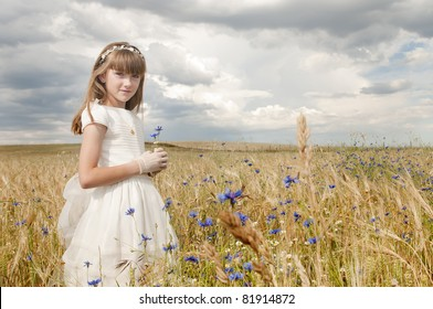 girl wearing first communion dress among the flowers