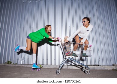 a girl wearing a green hoodie, sexy shorts, stockings and roller skates is pushing a supermarket trolley with a beautiful smiling girl standing in it