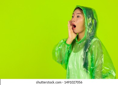 Girl is wearing a green rain dress on a green background.