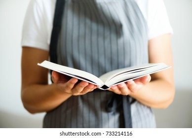 Girl wearing grey apron and reading book. Lifestyle concept