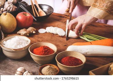 Girl wearing hanbok, making chopped kimchi, radish and carrots to mix with Chinese cabbage. Korean food concept from folk wisdom