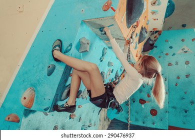 Girl wearing in harness and safety equipment climbing on practical wall indoor. Girl inserting the rope in a quickdraw. Focus on quickdraw