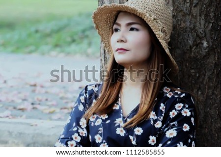 A girl wearing a hat sitting beside a tree in the forest with a lonely and sad expression.