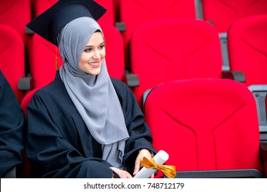 Girl wearing hijab graduation concept, red chairs, conference room