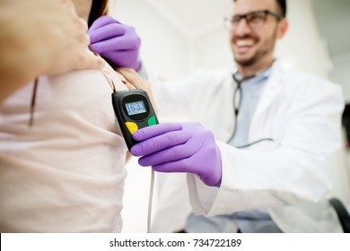 Girl wearing Holter monitor device for daily monitoring of an electrocardiogram checked by a smiling doctor.