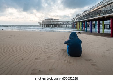 Girl wearing a hoodie sitting near the pier on the beach at sunset.