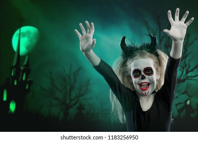 the girl wearing with horns. halloween make up. little girl scared on the background of the night