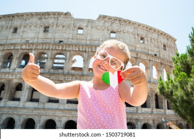 Girl Wearing Italian Flag Sunglasses, Holding Heart And Showing Thumb Up Near Colosseum, Rome, Italy