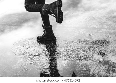 Girl wearing jeans and black combat boots splashing in a puddle after rain