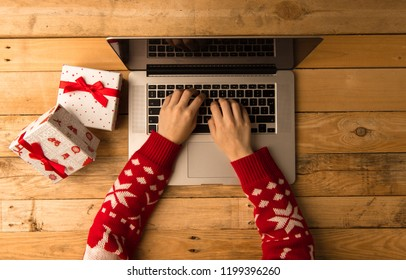 Girl wearing a jumper doing online shopping on her laptop