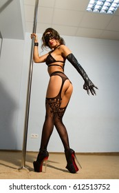girl wearing a lace mask and lingerie is dancing a striptease